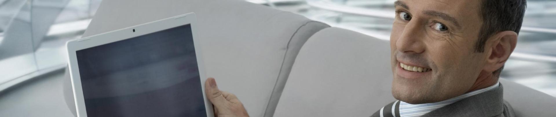 man zit met witte laptop op de bank