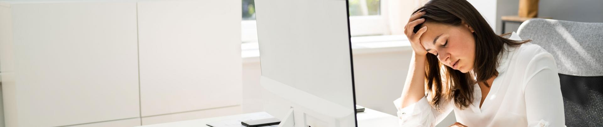 vrouw gestrest achter haar computer op het werk